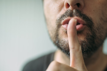 Finger on lips, man gesturing shhh sign