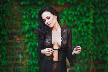 Beautiful hot female in underware posing in sensual way outdoors. Perfect, sexy body, belly and breast of young woman wearing seductive black lacy lingerie