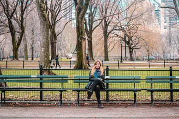 Gir sitting on a bench l in front of trees at the Central Park i