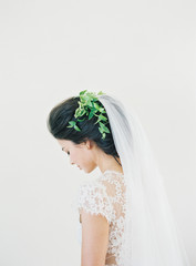 Bride wearing long veil and green leaves in hair