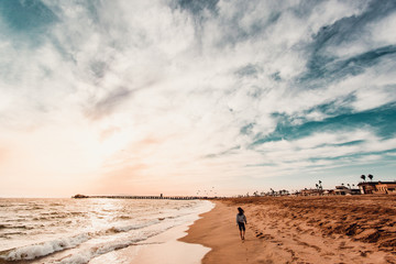 Person walking at waters edge on beach
