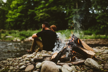 Couple sitting near campfire