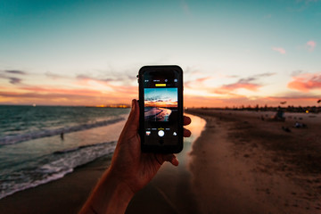 Person taking photo of beach on smartphone