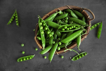 Fresh peas in basket on grey background