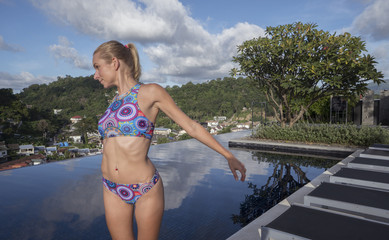 Pretty blonde happy woman wearing colourful bikini posing at rooftop infinity swimming pool on a sunny day over blue sky and city landscape