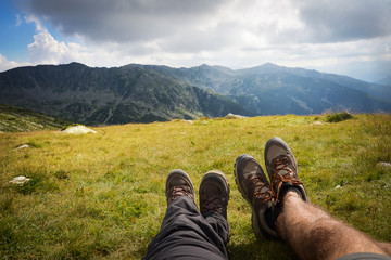 Couple's legs together on the rock on top of the hill with mountain ridge on the background. Hikers boots. Summer time, explore together
