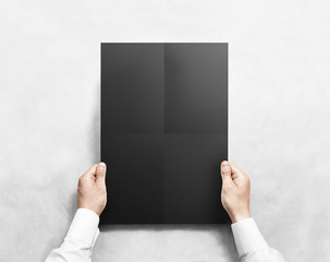 Hand holding black folded blank poster mockup, isolated. Arm in shirt hold clear broadsheet template mock up. Affiche bill design. Broadside pure print display show. Sticking a3 poster on the wall.