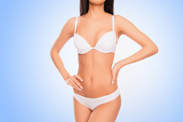 Close up of healthy slim woman's body isolated on blue backgroun
