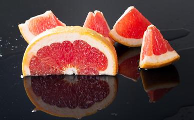 Half grapefruit citrus fruit on black background with water