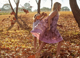 Young girls children kids playing running in fallen autumn leave