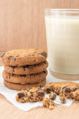 Chocolate chip cookies and a glass of milk on a wooden background.