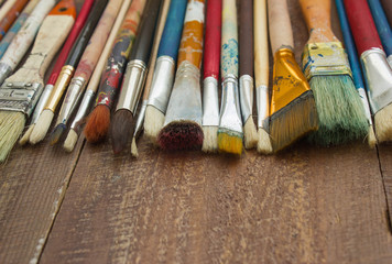 Brushes on a wooden background. The workplace of the artist. Banner for school