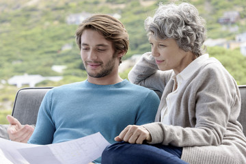 Happy mother with her adult son reading a blueprint outdoors