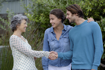 Happy mature woman meet with young couple outside