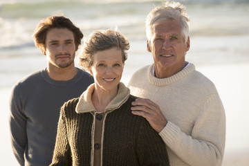 Portrait of happy family standing on the beach
