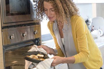Woman removing food tray from an oven