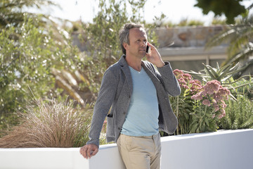 Man talking on a mobile phone in a garden