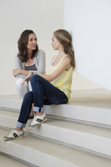 Mother and daughter talking to each other on steps
