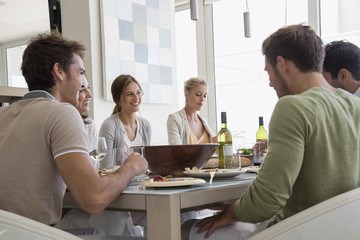 Group of happy friends having lunch at dining table