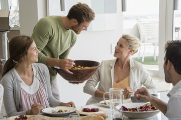 Young man serving food to her friends at dining table