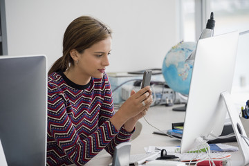 Businesswoman using a mobile phone while sitting in office