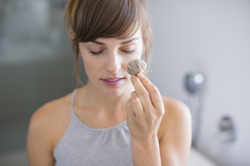 Woman applying face cosmetics