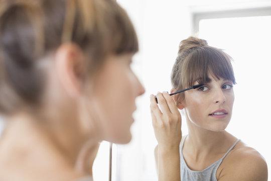Beautiful young woman applying mascara