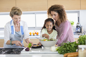 Senior woman with daughter and granddaughter preparing food in kitchen
