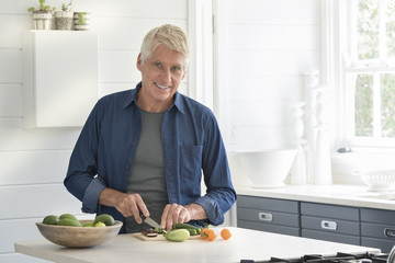 Happy senior man preparing vegetables in kitchen