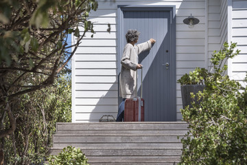Woman with suitcase knocking on door