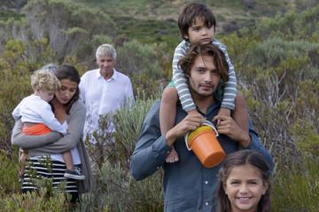 Happy multi-generation family walking on landscape