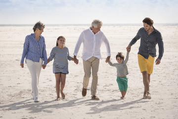 Happy multi-generation family walking on beach