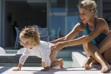 Young woman playing with her daughter at a resort