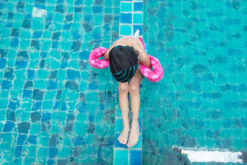 Happy little girl plaing in swimming pool