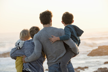Happy young family looking at sea on the beach at sunset