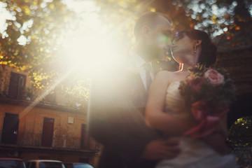 Sun shines behind a stunning kissing wedding couple