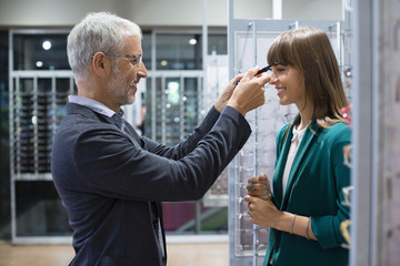 Shop assistant helping customer for trying on eyeglasses in optical shop