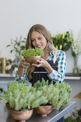 Happy female florist holding a potted plant