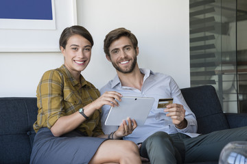 Happy couple shopping online on digital tablet