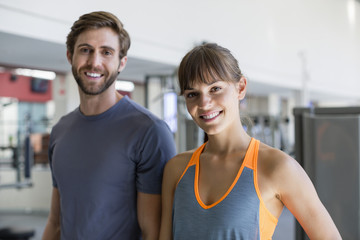 Happy young couple standing in a gym