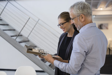 Design professionals examining architectural model in an office