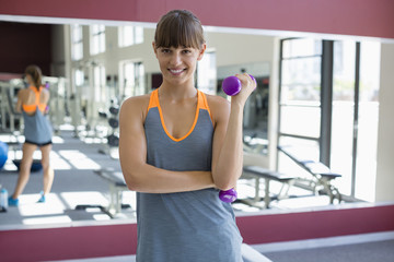 Happy young woman exercising with dumbbells in a fitness club