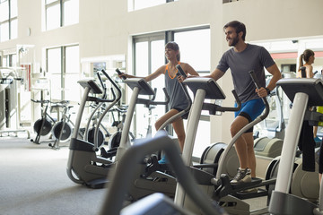 Young people exercising on machines in a health club
