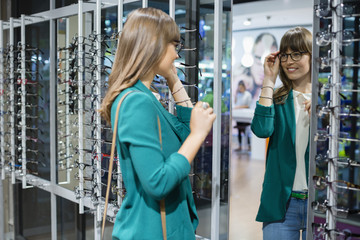 Young woman trying on eyeglasses in front of mirror in optical shop