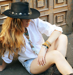 Young boho style woman have a rest sitting on a town street against old door, hippie, indie style