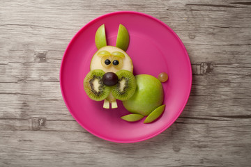 Rabbit made of fruits on plate and board
