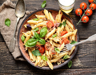 pasta with meat and basil on a plate on a wooden background