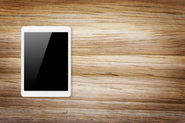 Digital tablet on wooden background.