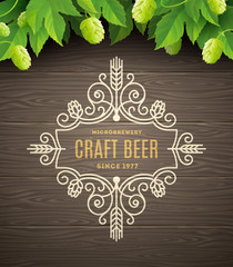 Green hops and flourishes beer emblem on a wooden plank background - vector illustration