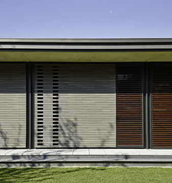 Back of house with wood slatted walls in white and red wood.